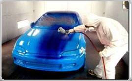Auto Body painter in paint booth painting car